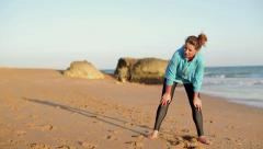 Tired woman catching breath during jogging on the beach HD Stock Footage