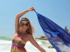 Happy young woman with blue pareo on the beach NTSC Stock Footage
