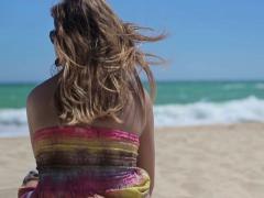 Woman in colorful dress relaxing on the beach NTSC Stock Footage