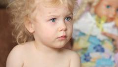 Serious two years old curly hair baby girl watching tv at home Stock Footage