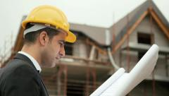 Man working, architect in construction site looking at building plans Stock Footage
