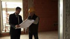 Plumber and architect talking and looking at blueprint in construction site Stock Footage