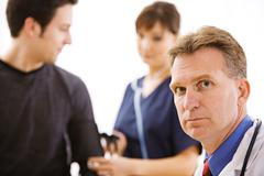 Doctors: serious doctor with patent and nurse Stock Photos