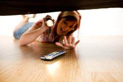 cleaning: excited to find remote under couch - stock photo