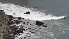 A Group of Surfers Practice, Tidal Waves Crashing, Jagged Rocks, People Surfing Stock Footage