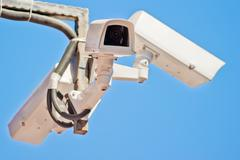 Three outdoor video surveillance camera on the bracket. Stock Photos