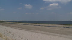 Pan new constructed port and reclaimed land, industrial area at horizon Stock Footage