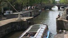 Canal boat in Amsterdam with tilt to the westertoren Stock Footage