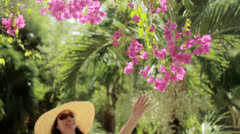 A woman caresses pink flowers 2 Stock Footage