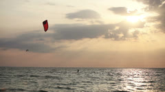 Kite surfer sailing  on the sea at sunset Stock Footage