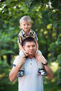 father and his baby son having fun in the park outdoor - stock photo