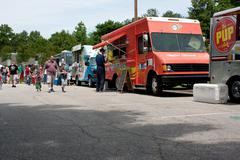 people buy meals from food trucks at festival - stock photo