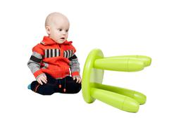 Stock Photo of child dropped a plastic chair in the studio