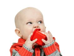 Little boy chewing on a plastic pyramid in the studio Stock Photos