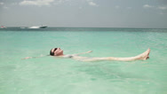 Stock Video Footage of A woman is floating in the turquoise water of the Caribbean.