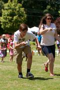 two people run in egg and spoon race at festival - stock photo