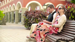 Happy young couple in tourist resort with tablet, cellphone, steadicam shot Stock Footage