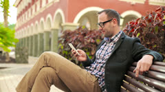 Young man with cellphone sitting on bench in tourist resort, steadicam shot Stock Footage
