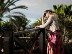Sad woman in tourist resort standing in the garden, steadicam shot Stock Footage
