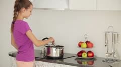 Girl is standing in the kitchen and stir the food in the pan Stock Footage