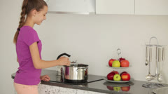 Girl prepares dinner and smiling at the camera Stock Footage