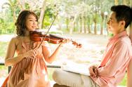 Stock Photo of woman playing violin with her boyfriend