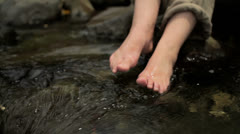 A woman cools her feet in a flowing creek 2 Stock Footage