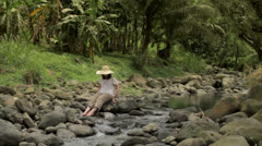 A woman cools her feet in a flowing creek 1 Stock Footage