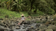 Stock Video Footage of A woman cools her feet in a flowing creek 1