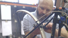 Man repairing bicycle in workshop Stock Footage