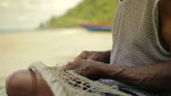Stock Video Footage of A fisherman repairs a fishing net
