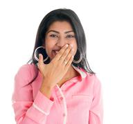 Indian woman giggles covering her mouth with hand Stock Photos