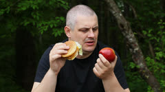 Man can not choose what to eat apple or burger episode 1 - stock footage