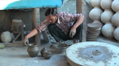 India Rajasthan Luni potter squeezes clay while wheel turns 2 Stock Footage