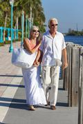 happy senior couple walking tropical sea or river - stock photo