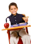 student: boy takes a bite from sandwich - stock photo