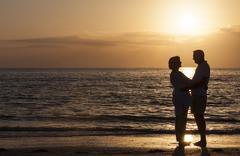 happy senior couple embracing on sunset beach - stock photo