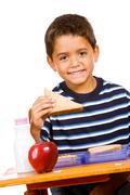 student: young student eating lunch at desk - stock photo