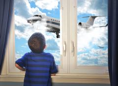boy looking at flying airplane in room - stock photo