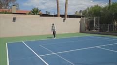Mature Tennis Pro - wide to medium serve approach and get ready Stock Footage