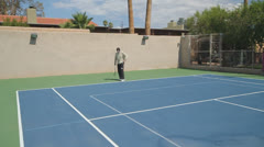 Mature Tennis Pro - wide shot power serve ace! Stock Footage
