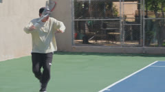 Mature Tennis Pro - slow motion forehand close Stock Footage