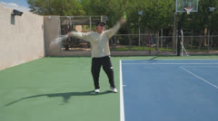 Mature Tennis Pro - med shot practice serves Stock Footage