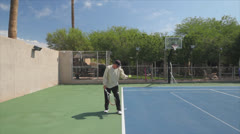 Mature Tennis Pro - wide shot practice warm up power serves Stock Footage