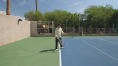 Mature Tennis Pro - wide shot practice overhead serves Stock Footage