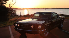 Sun sets on Mustang, ferry passes on waterway, 2000% Stock Footage