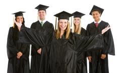 graduation: excited girl with other graduates behind - stock photo