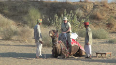 India Rajasthan Manvar camel kneels with passenger aboard Stock Footage