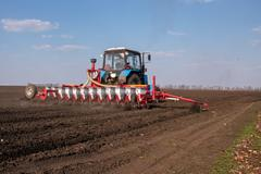 tractor with sower on the field - stock photo