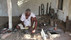India Rajasthan Manvar metal worker hammers on small anvil  - stock footage